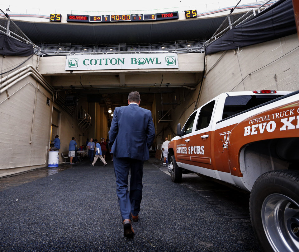 Photo - Head coach Bob Stoops heads to the dressing room after viewing the field before the Red River Showdown college football game between the University of Oklahoma Sooners (OU) and the University of Texas Longhorns (UT) at the Cottonbowl in Dallas, Texas on Saturday, Oct. 11, 2014. 