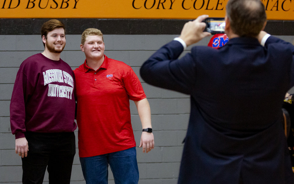 Photo - Missouri State University signee, Grant Goodson, left, and Southern Methodist University signee Ben Sparks pose for photos as they celebrate signing their letter of intent with classmates during a national signing day ceremony for football at Norman High School in Norman Okla. on Wednesday, Dec. 18, 2019.   [Chris Landsberger/The Oklahoman]