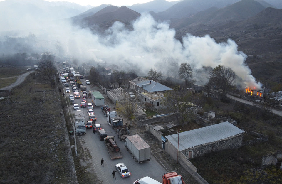 Photo -  Smoke rises from a burning house as cars and trucks stuck in a huge traffic jam climbing along the road from Kalbajar leaving the separatist region of Nagorno-Karabakh to Armenia, on Saturday, Nov. 14, 2020. The territory is to be turned over to Azerbaijan on Sunday as part of territorial concessions in an agreement to end six weeks of intense fighting with Armenian forces. Hundreds of thousands of Azeris were displaced by the war that ended in 1994. It is unclear when any civilians might try to settle in Karvachar — which will now be known by its Azeri name Kalbajar — or elsewhere. (AP Photo/Dmitry Lovetsky)