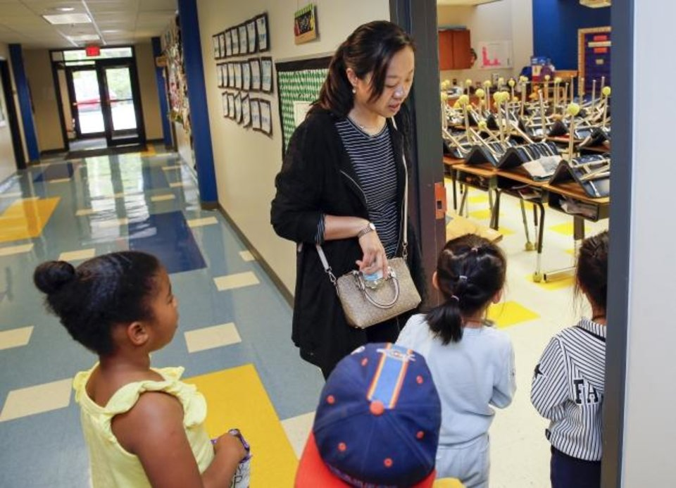 Photo -  Parent Angela Chen looks inside a classroom Saturday with her daughter Coco Chen, 6, second from right, while taking a tour with other students and parents during a POP-IN Open House for Oklahoma City Public Schools at Eugene Field Elementary. Coco Chen is at Gatewood now and is assigned to Eugene Field for first grade next year.  [Nate Billings/The Oklahoman]