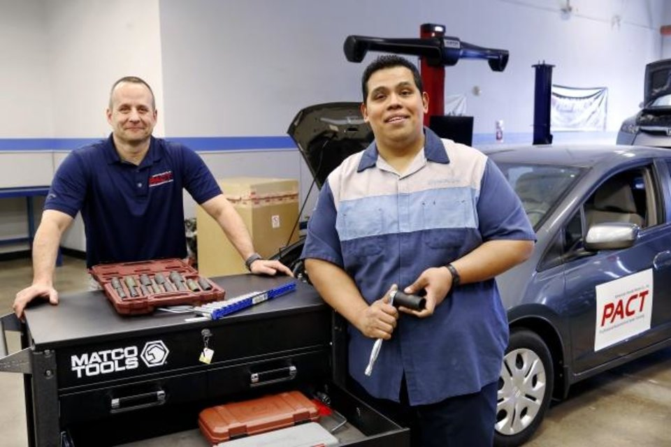Photo -  Luis Bondi, right, will graduate in May from the two-year Honda technician program at Oklahoma City Community College.  Bondi, 30, works full time at a dealership while earning his associate degree.  At left is Brad Walker,automotive department chair, who completed similar GM training at OCCC before becoming a mechanic and later an instructor. [Jim Beckel, The Oklahoman]