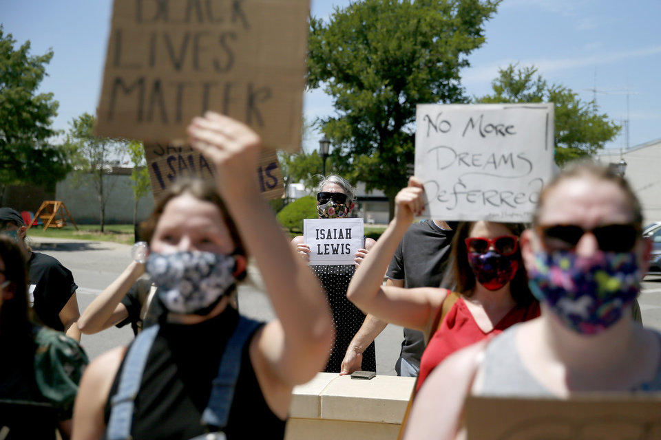 Photo - Protesters hold signs in front of the Edmond Police Department during a protest in Edmond, Okla., Saturday, June 6, 2020. The protest was organized in response to the shooting death of Isaiah Lewis by Edmond Police last year and the death of George Floyd in Minneapolis. [Bryan Terry/The Oklahoman]