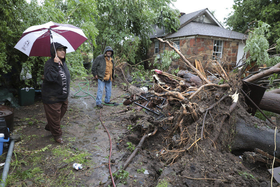 Photo - Carmen Perez and Jorge Torres survey storm damage of their home near Marshall and North Rockford in Tulsa on Tuesday, May 21, 2019. Their front door was blocked by a tree and they had to get out of their home through a front window. (Tom Gilbert/Tulsa World via AP)