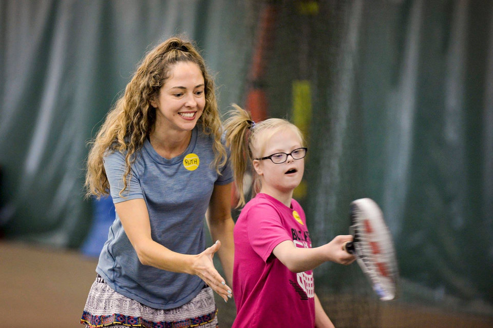 Photo - Volunteer Ruth helps Sydni Barnes with her swing during the We Are Champions Tennis Clinic at Kickingbird Tennis Center in Edmond. [PHOTO PROVIDED]