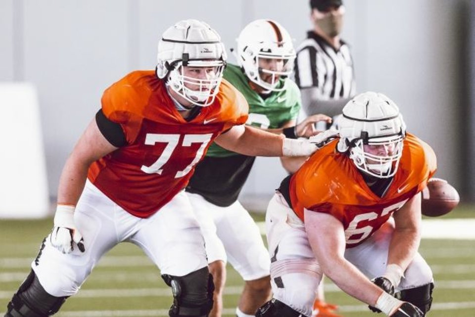 Photo -  Oklahoma State offensive linemen Hunter Anthony, left, and Cole Birmingham, right, block for quarterback Spencer Sanders during a drill at a recent practice. [Bruce Waterfield/Courtesy of OSU Athletics]