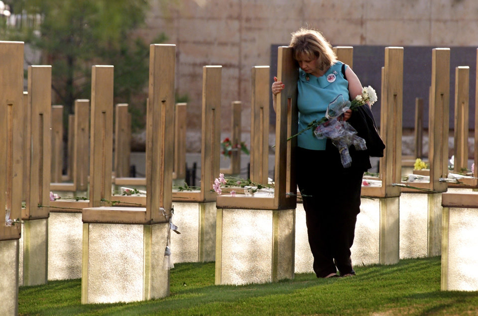 Photo - ALFRED MURRAH FEDERAL BUILDING CAR BOMB EXPLOSION, BOMBING, ANNIVERSARY: Oklahoma City National Memorial:  Ginny Moser places flowers and hugs memorial chairs at the April 19, 2002 ceremony.  Staff photo by Steve Sisney