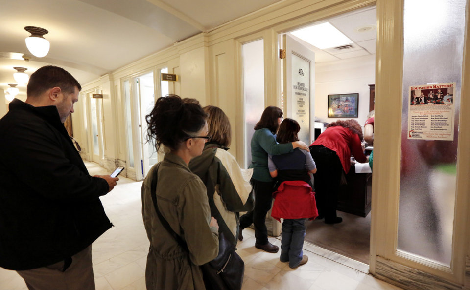 Photo - People stand in the hallway waiting to sign in at Sen. Rob Standridge's office at the Capitol. Advocates for mental health care descended upon the state Capitol Tuesday morning, Oct. 24, 2017, to demand that lawmakers come up with a budget solution that includes funding for mental health services. Photo by Jim Beckel, The Oklahoman