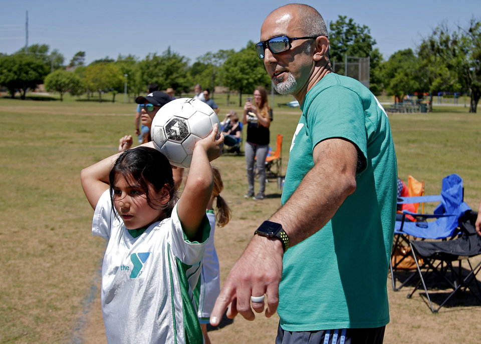Photo -  Estabraq Al-Adhami coaches his daughter Hala, 9, during a soccer game in Oklahoma City. [Photo by Bryan Terry, The Oklahoman]