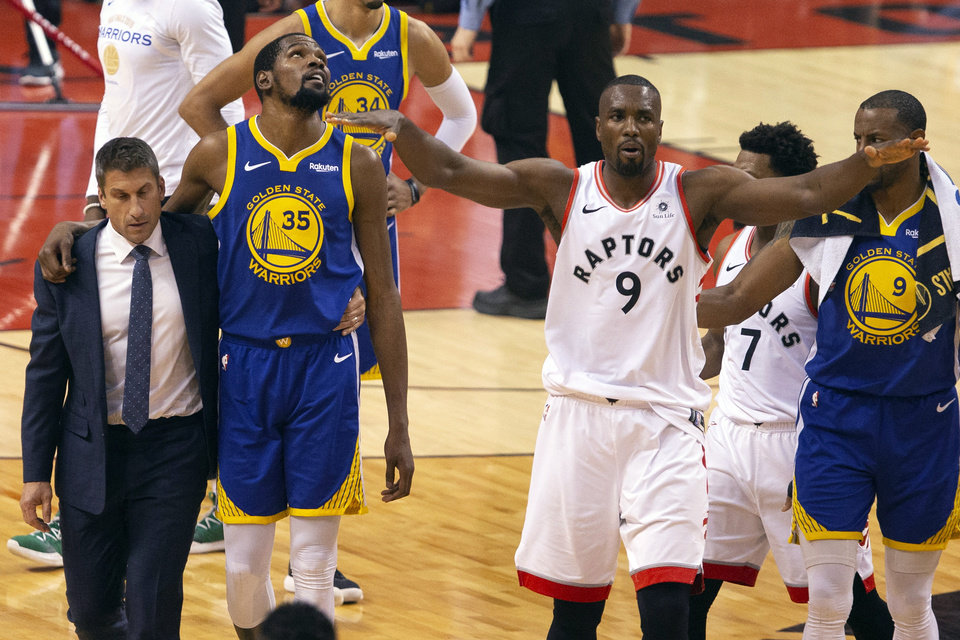 Photo - Golden State Warriors forward Kevin Durant (35) walks off the court after sustaining an injury as Toronto Raptors center Serge Ibaka (9) gestures to the crowd during first half basketball action in Game 5 of the NBA Finals in Toronto on Monday, June 10, 2019. (Chris Young/The Canadian Press via AP)
