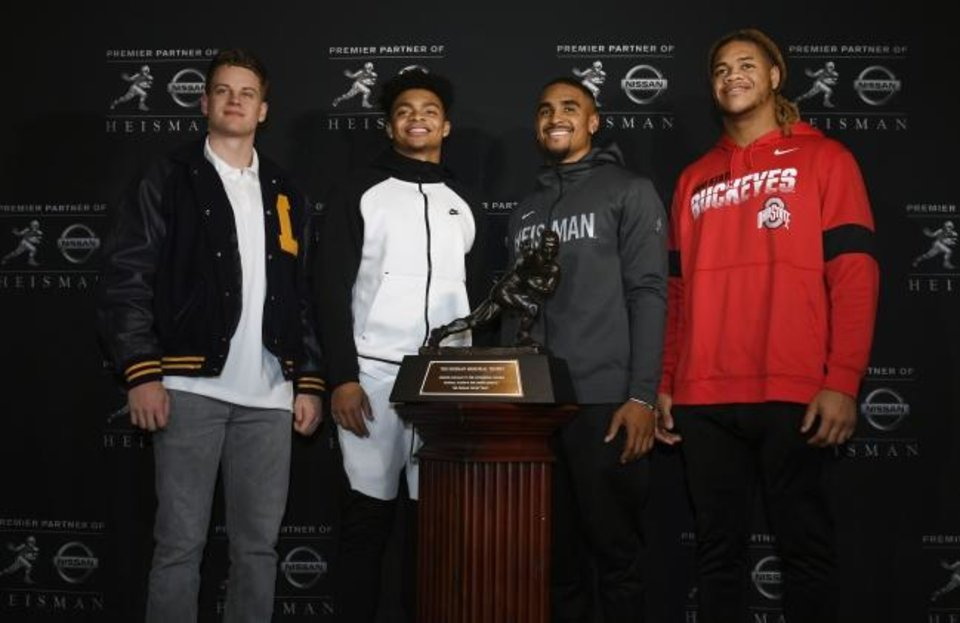 Photo -  (From left): Heisman finalists Joe Burrow of LSU, Justin Fields of Ohio State, Jalen Hurts of Oklahoma and Chase Young of Ohio State pose with the trophy Friday in New York. [Todd Van Emst/Heisman Trust]