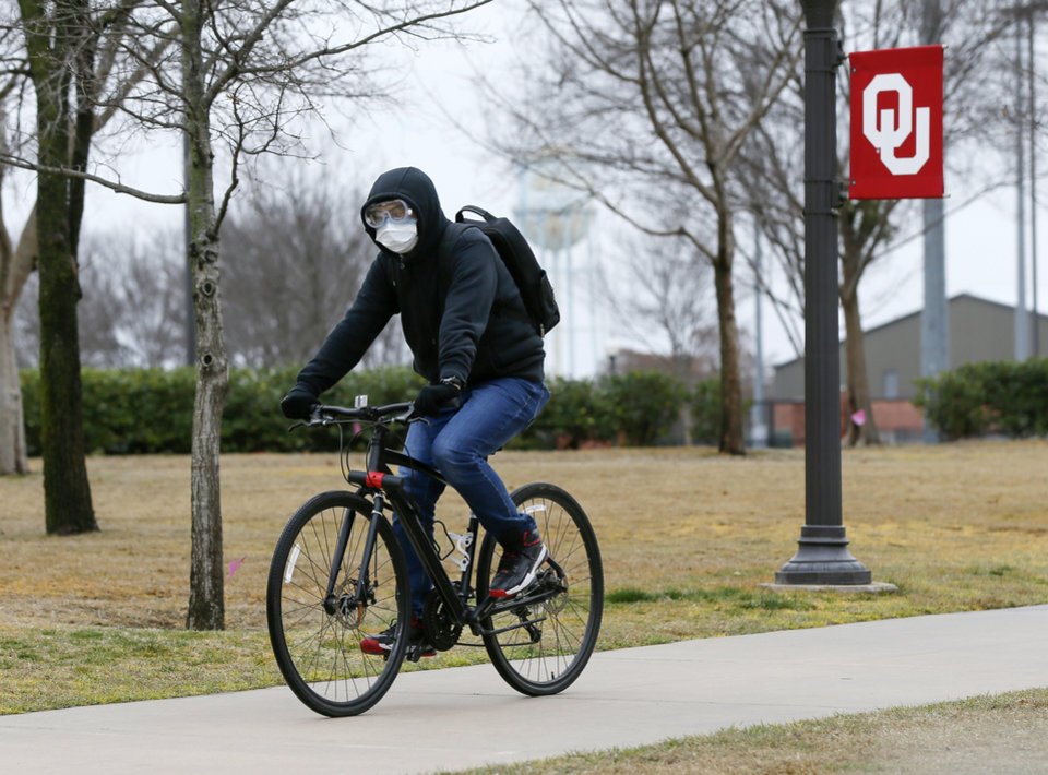 Photo - A cyclist wears a mask and googles while riding north on a sidewalk along Jenkins Ave. on the University of Oklahoma campus in Norman, Okla., Tuesday, March 17, 2020. [Nate Billings/The Oklahoman]