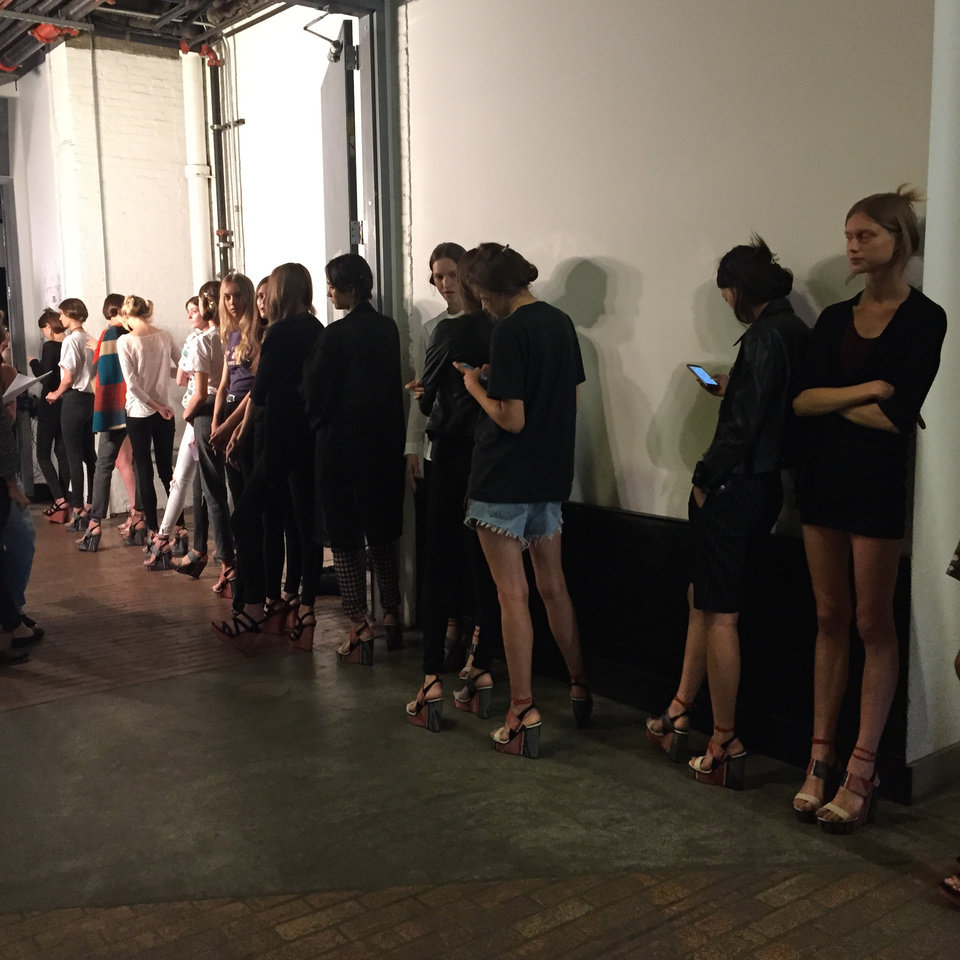 Photo - Models wait in line to practice their runway walk before the Adeam show.