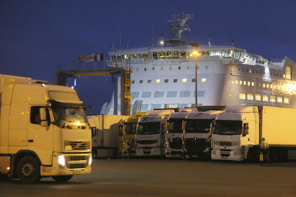 Photo -  Trucks park as a ferry coming from Britain's port of Portsmouth docks at the transit zone at the port of Ouistreham, Normandy, Thursday, Sept.12, 2019. France has trained 600 new customs officers and built extra parking lots arounds its ports to hold vehicles that will have to go through extra checks if there is no agreement ahead of Britain's exit from the EU, currently scheduled on Oct. 31. (AP Photo/David Vincent)