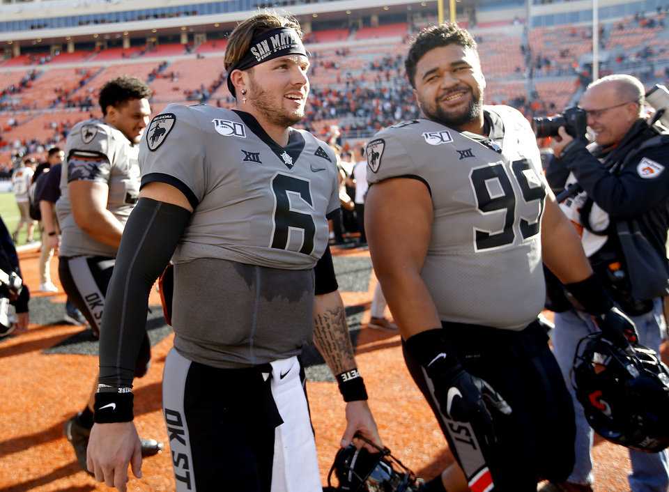 Photo - Oklahoma State's Dru Brown (6) walks off with Sione Asi (99) following the college football game between the Oklahoma State University Cowboys and the Kansas Jayhawks at Boone Pickens Stadium in Stillwater, Okla., Saturday, Nov. 16, 2019. OSU won 31-13. [Sarah Phipps/The Oklahoman]