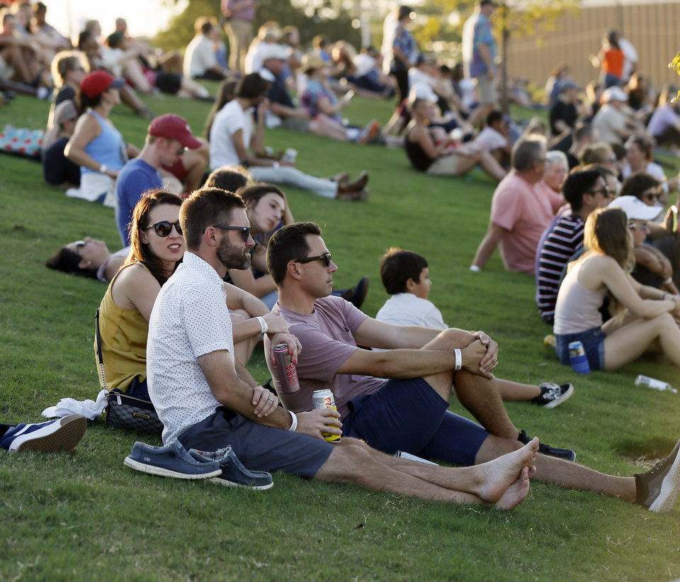 Photo - People watch the concert from the hill during the grand opening of Scissortail Park in Oklahoma City, Friday, Sept. 27, 2019. [Nate Billings/The Oklahoman]