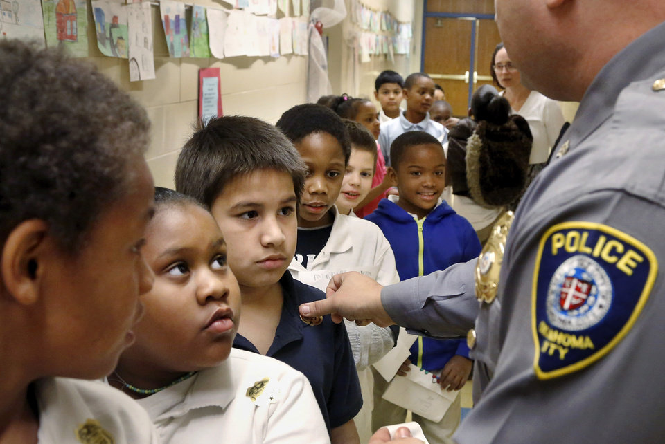 Photo - Oklahoma City police officer Tomas Daughtery visits students and staff Feb. 19 at Bodine Elementary School in southeast Oklahoma City. The principal is Nikki Coshow.  Bodine is one of four elementary schools that police are focusing on in an attempt to reduce higher school violence statistics.  School district safety director Rod McKinley has enacted a plan to to put more officers in schools, with a goal of providing a safer learning environment.  Photos by Jim Beckel, The Oklahoman   Jim Beckel