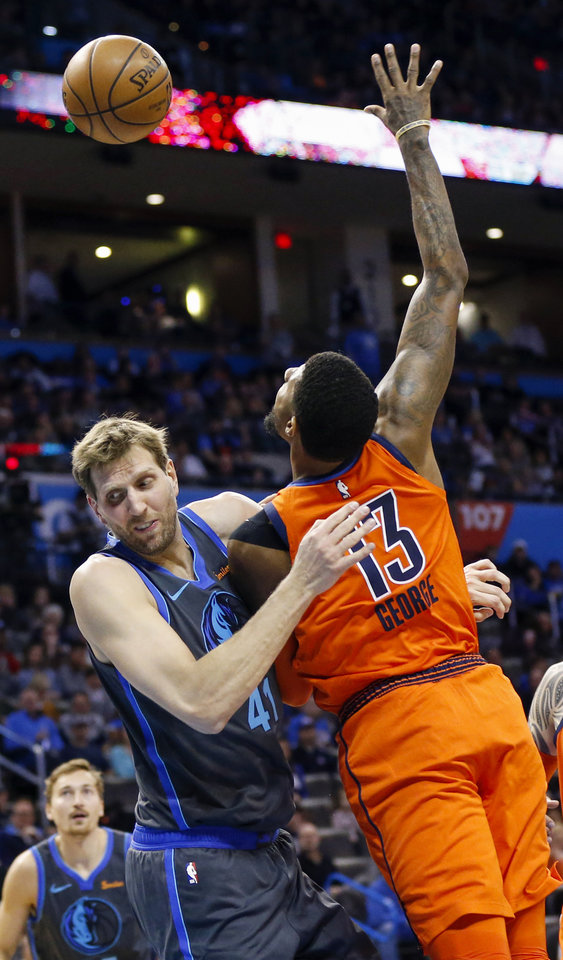 Photo - Oklahoma City's Paul George (13) is fouled by Dallas' Dirk Nowitzki (41) in the second quarter during an NBA basketball game between the Dallas Mavericks and the Oklahoma City Thunder at Chesapeake Energy Arena in Oklahoma City, Sunday, March 31, 2019. Photo by Nate Billings, The Oklahoman