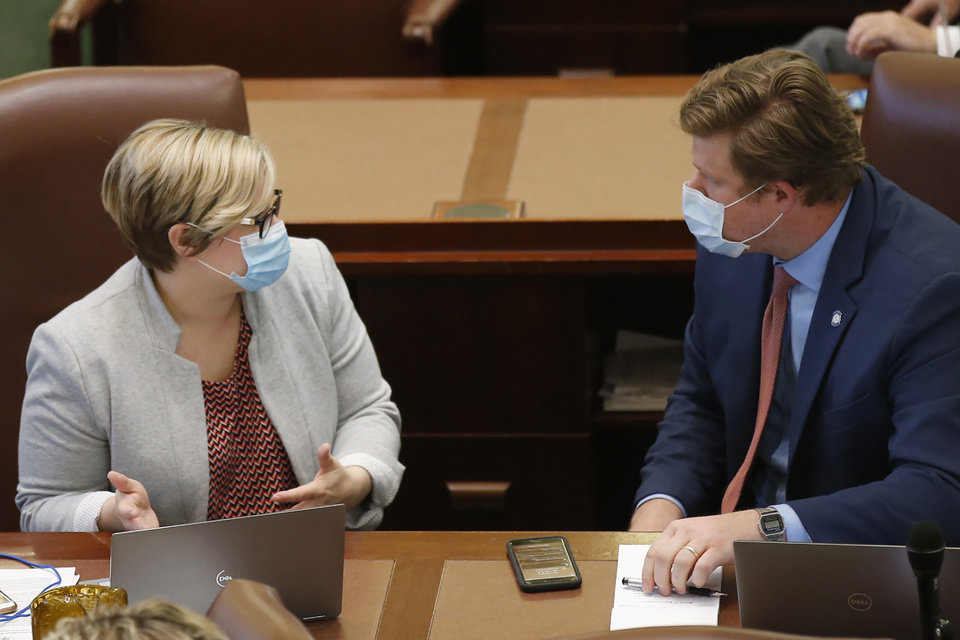 Photo - Oklahoma state Reps. Emily Virgin, left, D-Norman and Forrest Bennett, right, D-Oklahoma City, talk on the House floor Wednesday, May 6, 2020, in Oklahoma City. Just days after the Oklahoma Supreme Court ruled absentee ballots in Oklahoma don't need to be notarized, the House on Wednesday passed a bill imposing new restrictions on voters who cast ballots by mail. (AP Photo/Sue Ogrocki)