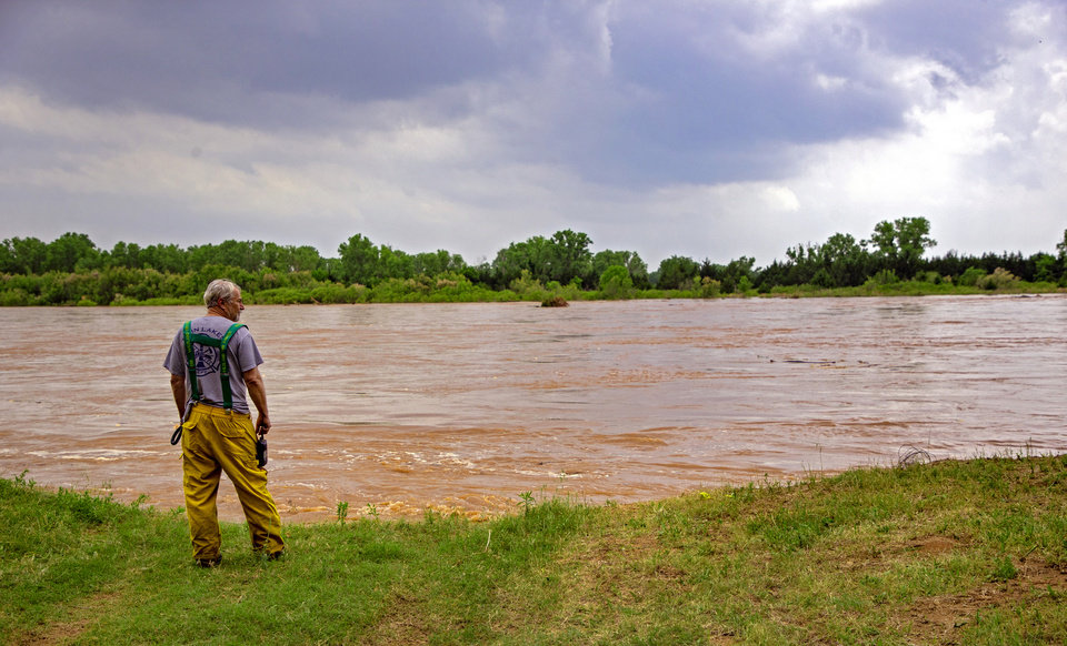 Photo - Fire Chief Mike Gilliam looks on as he watches flood waters from the Cimarron River threaten homes in the Twin Lakes community near Cimarron City, Okla. on Wednesday, May 22, 2019.  [Chris Landsberger/The Oklahoman]
