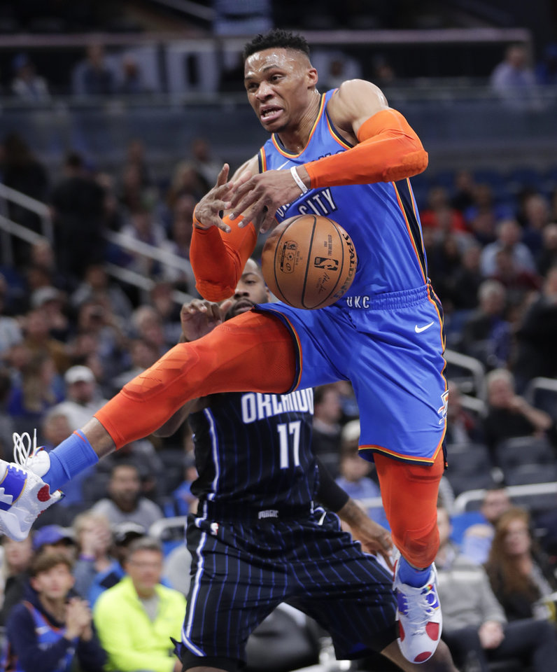Photo - Oklahoma City Thunder's Russell Westbrook, right, loses control of the ball going up for a shot after he was fouled by Orlando Magic's Jonathon Simmons (17) during the first half of an NBA basketball game, Tuesday, Jan. 29, 2019, in Orlando, Fla. (AP Photo/John Raoux)