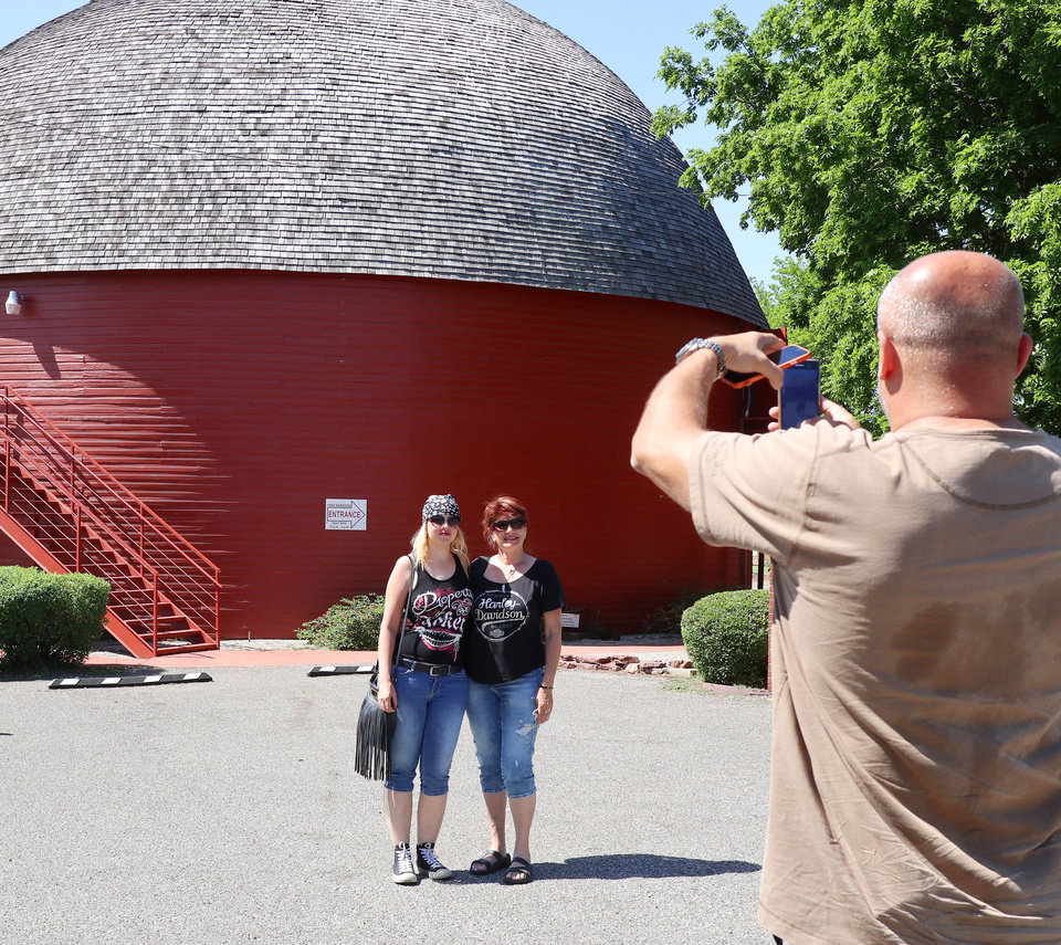Photo -  Monika Kerkova, left, and Olga Horinkova, with a group of tourists from the Czech Republic, have their photo taken at the Round Barn. [Photo by Doug Hoke, The Oklahoman]