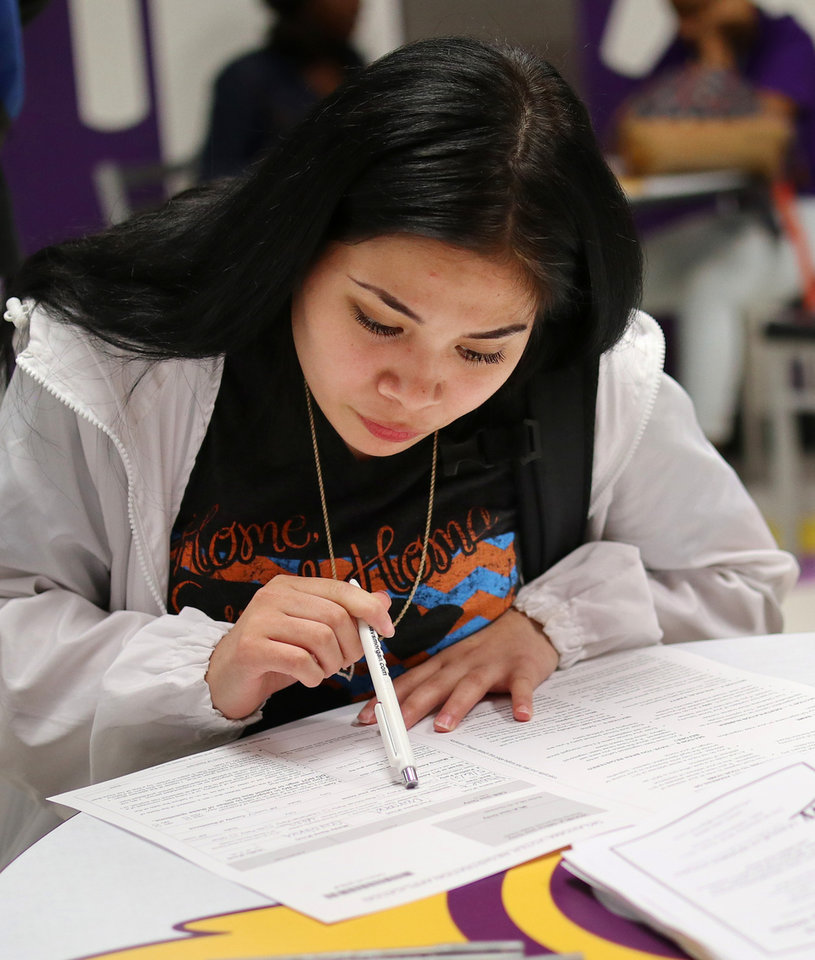 Photo - Diamond Alvarez, 18, fills out a registration form. Generation Citizen set up at Northwest Classen High School during lunch to register students age 17 and older to vote, Wednesday, September 25, 2019. [Doug Hoke/The Oklahoman]