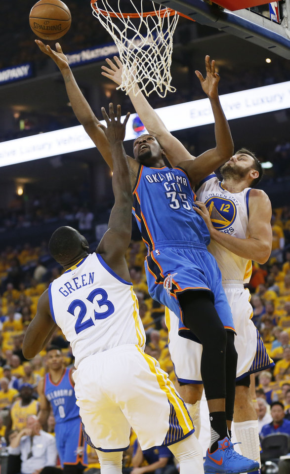 Photo - Oklahoma City's Kevin Durant (35) goes to the basket between Golden State's Draymond Green (23) and Andrew Bogut (12) during Game 2 of the Western Conference finals in the NBA playoffs between the Oklahoma City Thunder and the Golden State Warriors at Oracle Arena in Oakland, Calif., Wednesday, May 18, 2016. Photo by Nate Billings, The Oklahoman