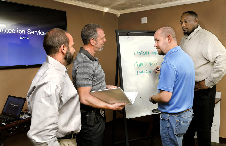 Photo -  Grady Hendrickson, third from left, owns Hendrickson Investigation & Protection LLC, which is now offering services to marijuana companies, including transportation of money and securing their buildings and inventory. Hendrickson works with members of Cloaked Industries, including from left, Cloaked Industries Vice President Kimes Branning, Cloaked Industries President Nick Balan and, at right, Cloaked Industries Security Officer Dontavio Hines. [Jim Beckel/The Oklahoman]