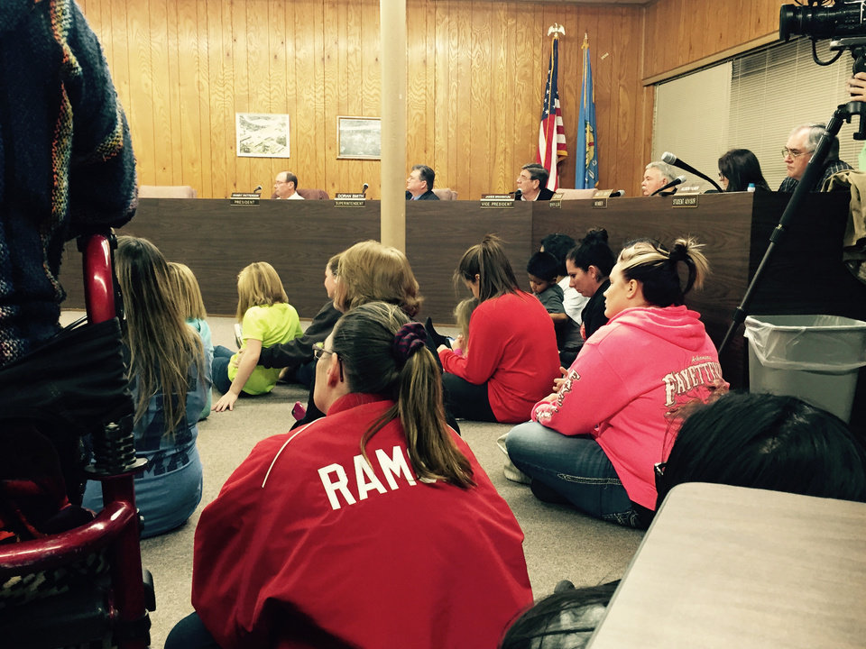 Photo -  People sit on the ground Thursday night in McLoud as they listen to the town's school board meeting. Many more stood in and around the doorway. The McLoud School Board voted to keep the controversial Redskins mascot in place Thursday night, despite strong opposition.