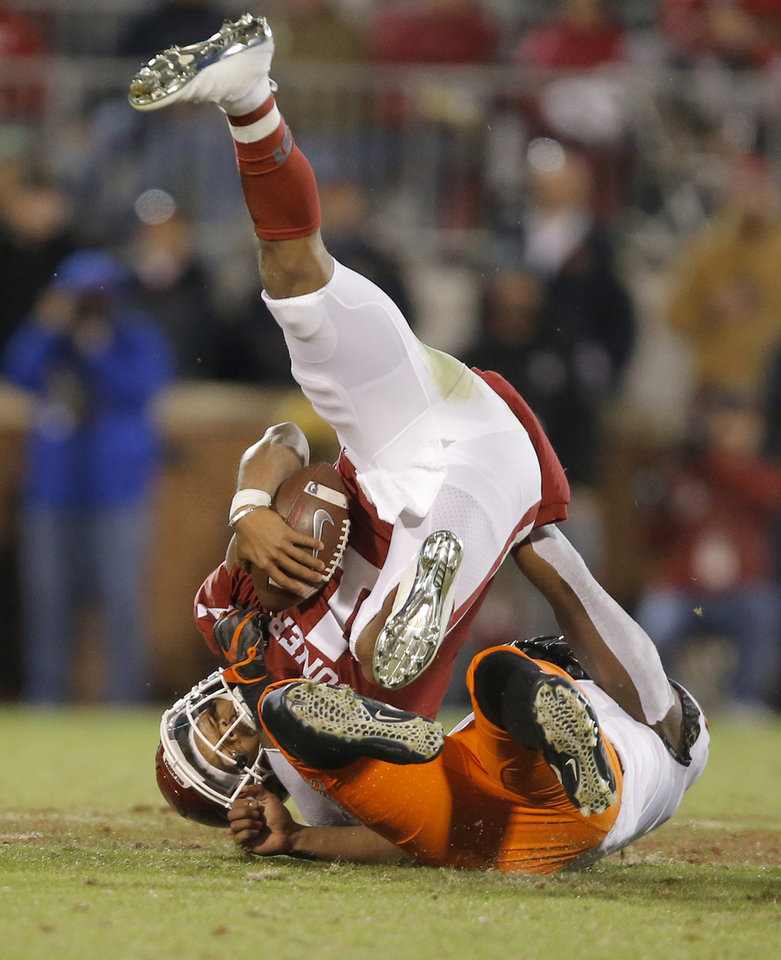 Photo - Oklahoma State's Amen Ogbongbemiga (11) bring down Oklahoma's Kyler Murray (1) during a Bedlam college football game between the University of Oklahoma Sooners (OU) and the Oklahoma State University Cowboys (OSU) at Gaylord Family-Oklahoma Memorial Stadium in Norman, Okla., Nov. 10, 2018.  Photo by Bryan Terry, The Oklahoman