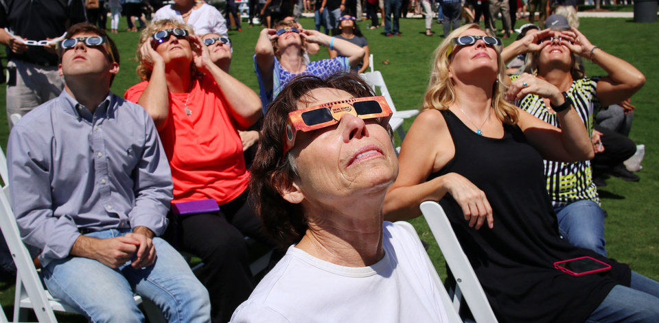 Photo -  Sueann Burton and others behind her watch the eclipse Monday from the Great Lawn of the Myriad Botanical Gardens. [Photo by Doug Hoke, The Oklahoman]