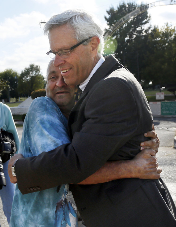 Photo - Don Knight, right, attorney for Richard Glossip, gets a hug from Carl Oldham, a family friend of Glossip from Wright City, Okla., after the scheduled execution of Richard Eugene Glossip was stayed at the Oklahoma State Penitentiary in McAlester, Okla., Wednesday, Sept. 30, 2015. Gov. Fallin stayed the execution for 37 days. Photo by Nate Billings, The Oklahoman
