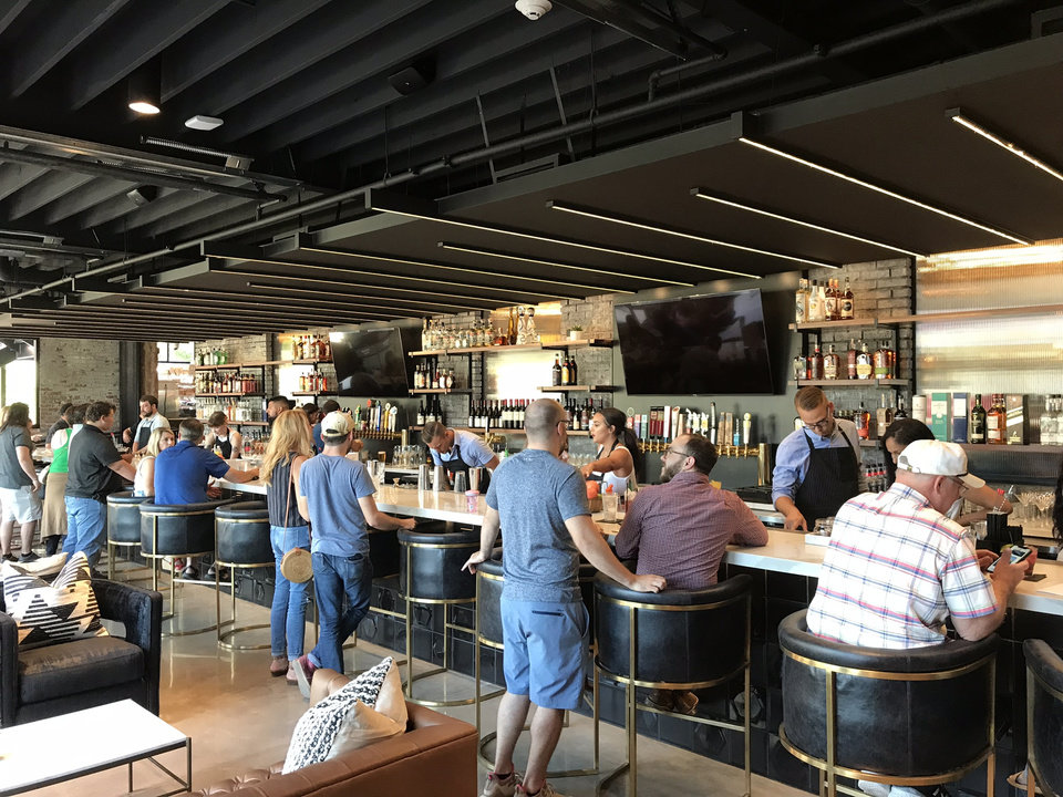 Photo - The bar fills up inside The Collective, a new food hall in downtown Oklahoma City. [Dave Cathey/The Oklahoman]