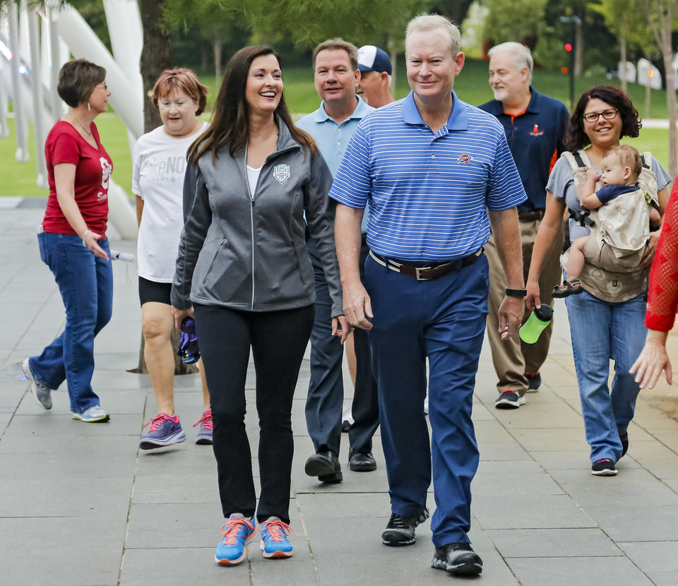 Photo - Mayor Mick Cornett walks with his wife Terri as they lead a group of walkers during a heart health walk around the Myriad Botanical Gardens in Oklahoma City, Okla. on Friday, Sept. 16, 2016. Photo by Chris Landsberger, The Oklahoman