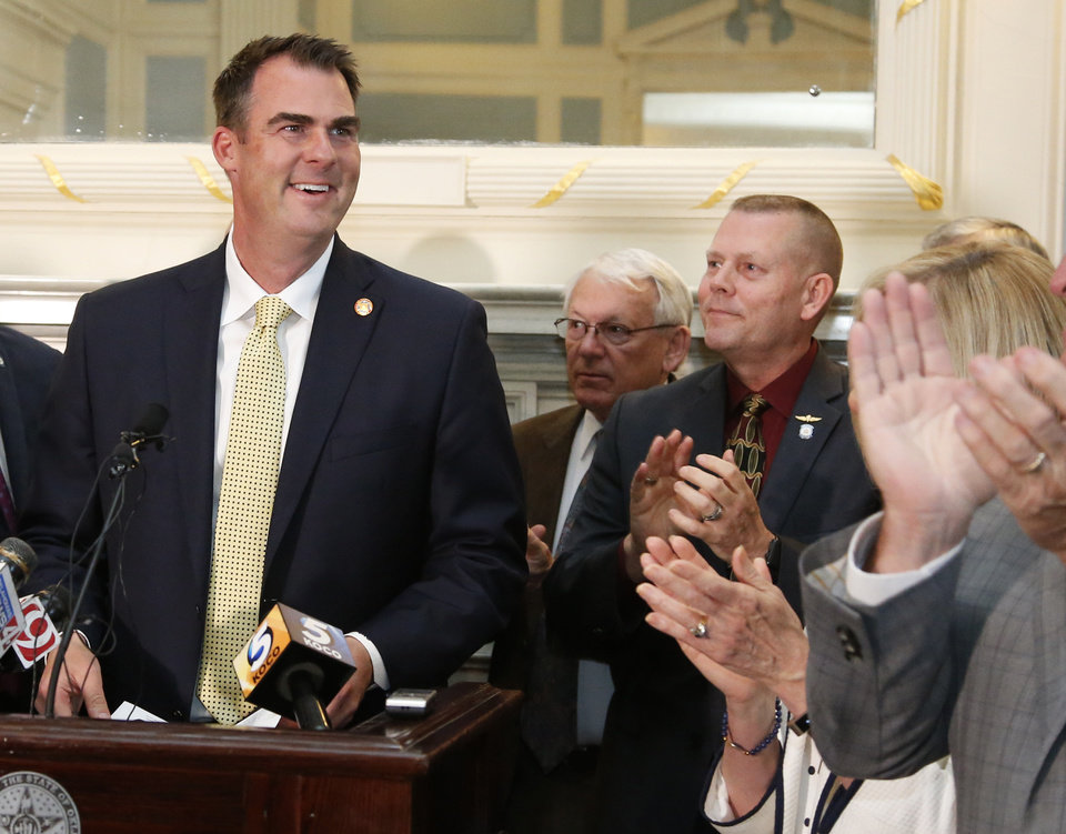 Photo - Oklahoma Gov. Kevin Stitt, left, is applauded as he arrives for a joint news conference with Republican legislative leaders to announce a deal on a $8.3 billion budget for the upcoming fiscal year that includes an average $1,200 pay raise for teachers and tens of millions more dollars for schools, Wednesday, May 15, 2019, in Oklahoma City. (AP Photo/Sue Ogrocki)
