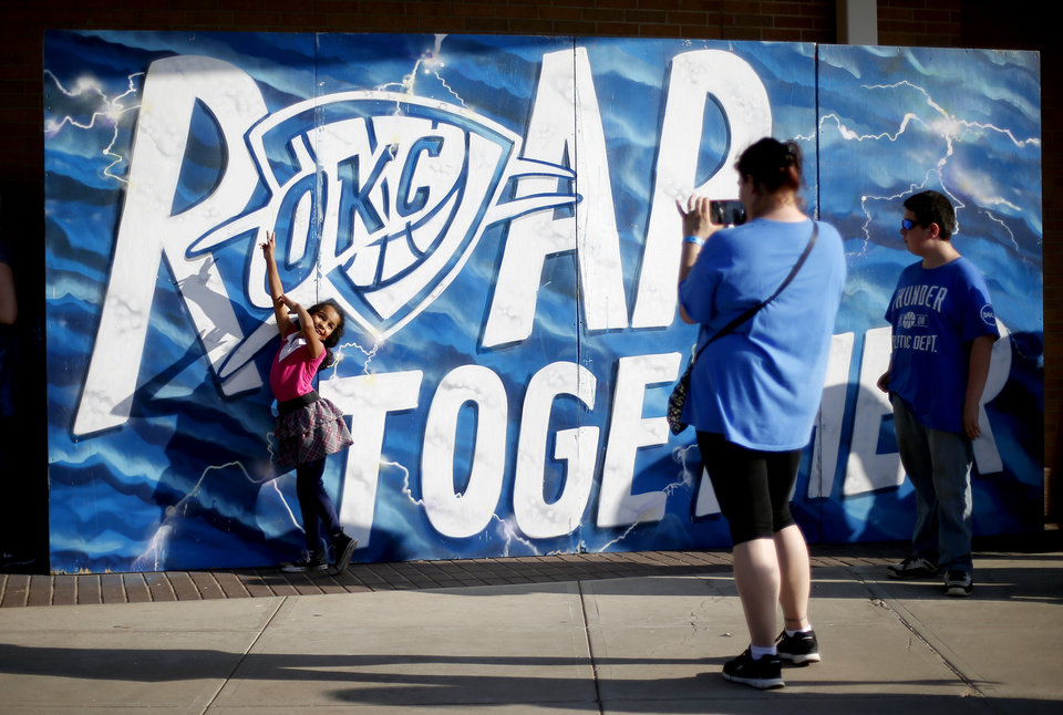 Photo - Tiffany Cook of Oklahoma City takes a picture of her daughter Jade Cook, 6, outside Chesapeake Energy Arena before  Game 6 of the Western Conference finals in the NBA playoffs between the Oklahoma City Thunder and the Golden State Warriors at Chesapeake Energy Arena in Oklahoma City, Saturday, May 28, 2016. Photo by Bryan Terry, The Oklahoman