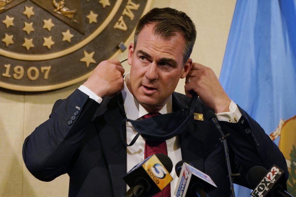 Photo - Gov. Kevin Stitt removes his face covering before speaking at a news conference in Oklahoma City, Monday, Nov. 16, 2020. [AP Photo/Sue Ogrocki]