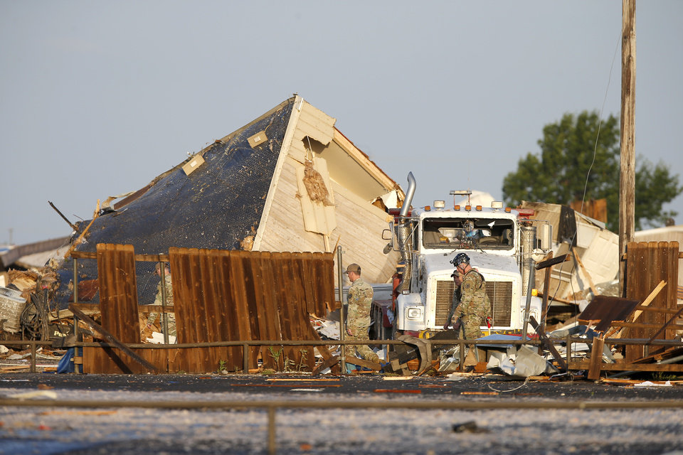 Photo - Workers looks through tornado damage  to mobil homes near the American Budget Value Inn in El Reno, Okla., Sunday, May 26, 2019. [Bryan Terry/The Oklahoman]