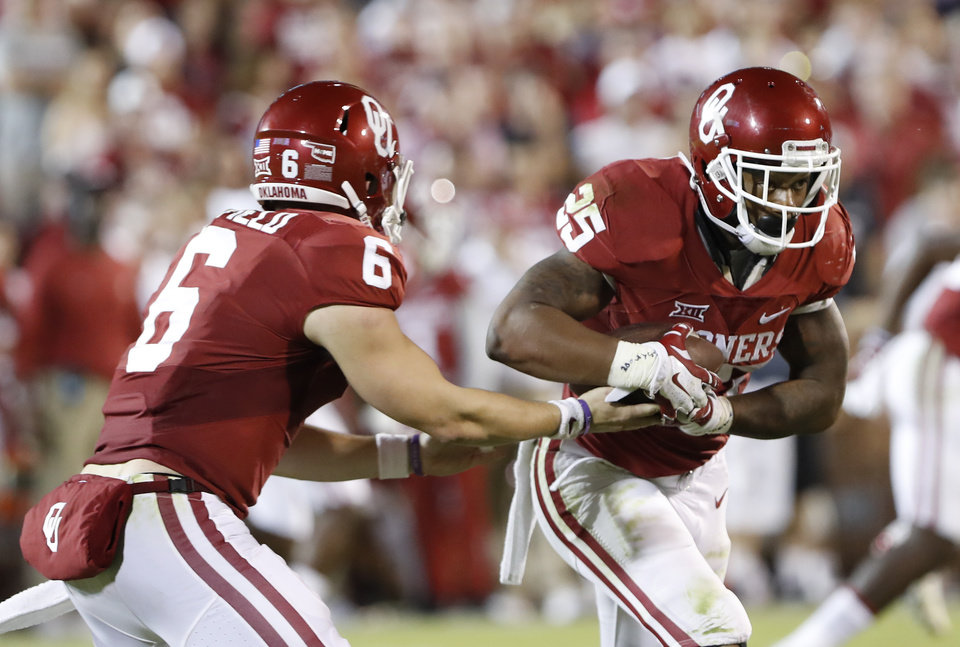 Photo -  Oklahoma quarterback Baker Mayfield, left, hands off the ball to running back Joe Mixon on Saturday. [AP Photo]