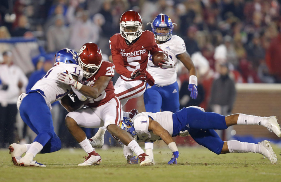 Photo - Oklahoma's Marquise Brown (5) tries to leap over Kansas' Bryce Torneden (1) during a college football game between the University of Oklahoma Sooners (OU) and the Kansas Jayhawks (KU) at Gaylord Family-Oklahoma Memorial Stadium in Norman, Okla., Saturday, Nov. 17, 2018. Photo by Bryan Terry, The Oklahoman