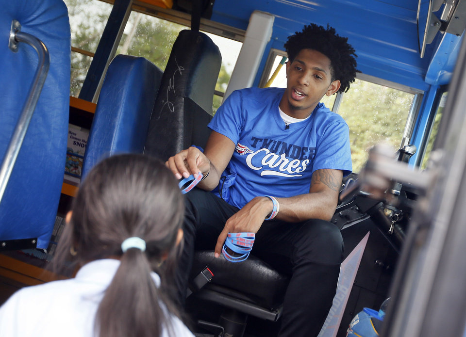 Photo - Oklahoma City guard Cameron Payne hands a bracelet to a student as she boards the Oklahoma City Thunder's Rolling Thunder Book Bus to pick out a free book at Sequoyah Elementary, 2400 NW 36th St., in Oklahoma City, Thursday, Sept. 15, 2016. Photo by Nate Billings, The Oklahoman