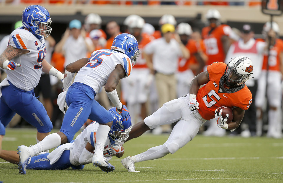 Photo - Oklahoma State's Justice Hill (5) fights fro more yards as Boise State's DeAndre Pierce (4) brings him down during a college football game between the Oklahoma State University Cowboys (OSU) and the Boise State Broncos at Boone Pickens Stadium in Stillwater, Okla., Saturday, Sept. 15, 2018. Oklahoma State won 44-21. Photo by Bryan Terry, The Oklahoman