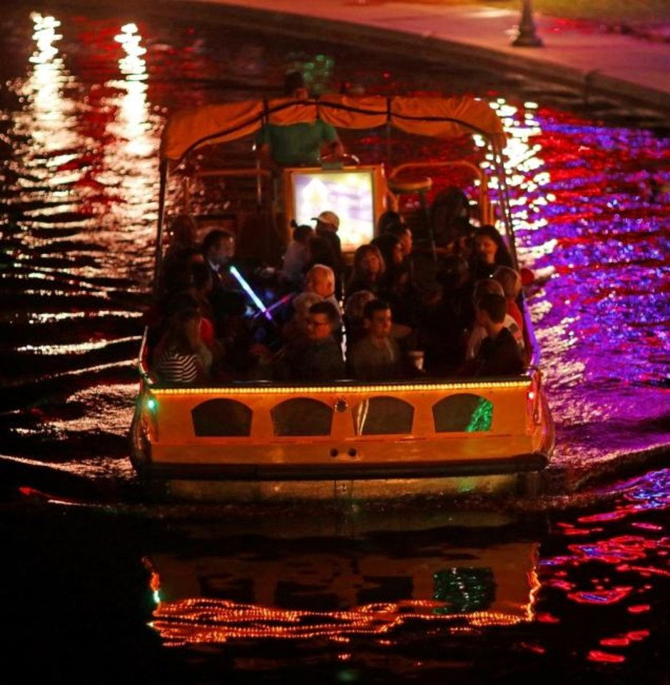 Photo -  People take advantage of a free Holiday Water Taxi ride to see the Bricktown Canal Lights as part of 2017's Downtown in December. [Doug Hoke/The Oklahoman Archives]