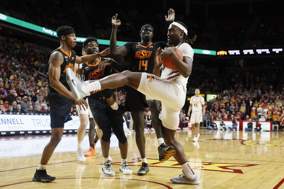 Photo - Iowa State forward Solomon Young, right, grabs a rebound in front of Oklahoma State forward Yor Anei (14) during the first half of an NCAA college basketball game, Tuesday, Jan. 21, 2020, in Ames, Iowa. (AP Photo/Charlie Neibergall)