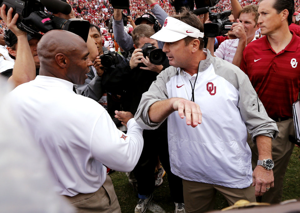 Photo - Head coaches Charlie Strong and Bob Stoops meet at midfield after the Red River Showdown college football game where the University of Oklahoma Sooners (OU) defeated the University of Texas Longhorns (UT)  31-26 at the Cotton Bowl in Dallas, Texas on Saturday, Oct. 11, 2014. 