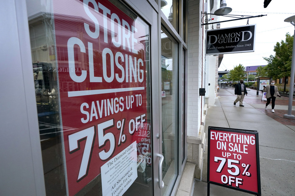 Photo -  Passers-by walk past a business storefront with store closing and sale signs, Wednesday, Sept. 2, 2020, in Dedham, Mass.  A critical snapshot of the job market and the economy to be released Friday, Oct. 2,  is expected to show a further deceleration in hiring as the nation's viral caseload creeps higher just as financial aid from the government has faded. (AP Photo/Steven Senne)