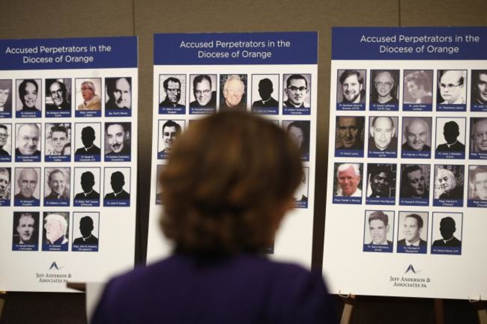 Photo -  An advocate and survivor of sexual abuse looks at the photos of Catholic priests accused of sexual misconduct by victims during a news conference in Orange, Calif. [Jae C. Hong/AP Photo]