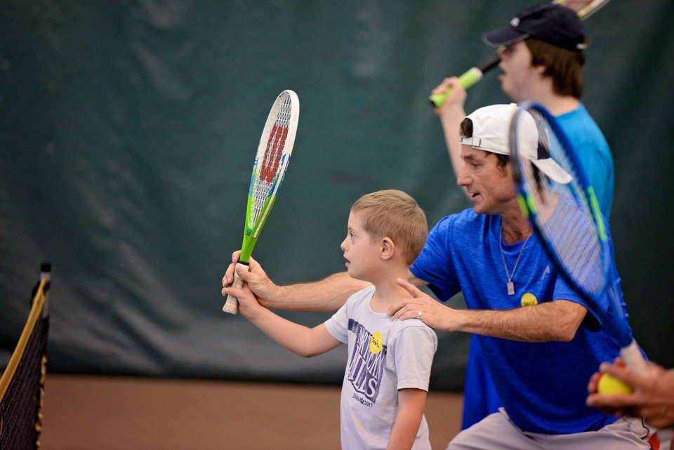 Photo - David Kepka helps Josh Spangler position his racket during a We Are Champions Tennis Clinic at Kickingbird Tennis Center in Edmond. [PHOTO PROVIDED]