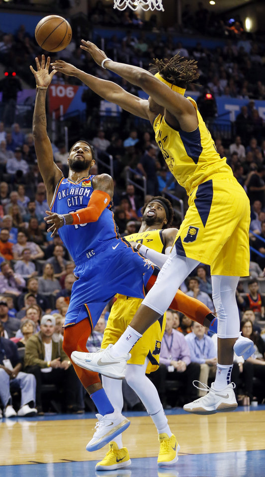 Photo - Oklahoma City's Paul George (13) shoots between Indiana's Wesley Matthews (23), back, and Myles Turner (33) during an NBA basketball game between the Indiana Pacers and the Oklahoma City Thunder at Chesapeake Energy Arena in Oklahoma City, Wednesday, March 27, 2019. Photo by Nate Billings, The Oklahoman