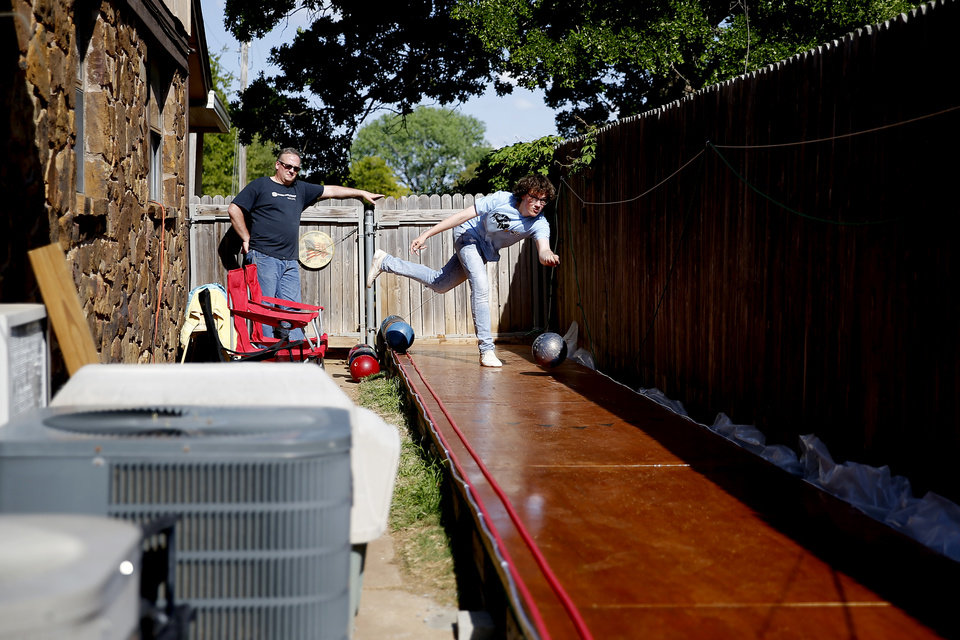 Photo - Eric Jones, 15, bowls as he dad Heath watches in the backyard of their Oklahoma City home, Tuesday, April 21, 2020. Health and his son Eric built a bowling lane in their backyard so that Eric, a competitive bowler, could continue to bowl while bowling alleys are closed.. [Bryan Terry/The Oklahoman]